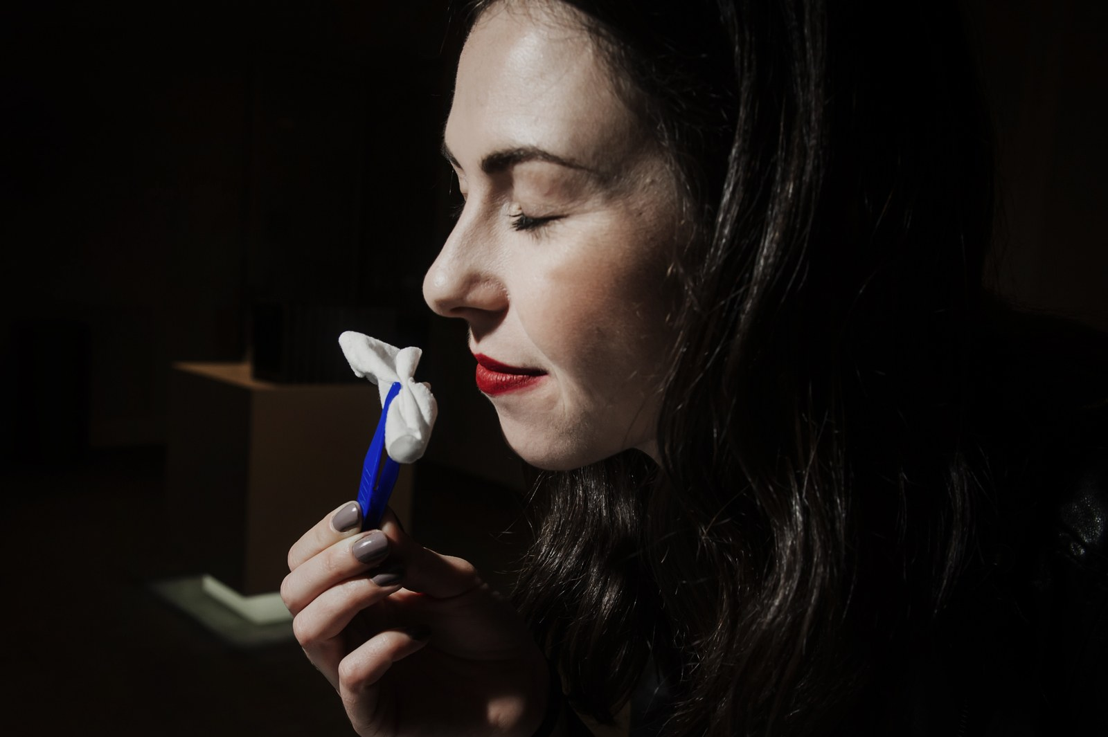 a woman sniffing an object