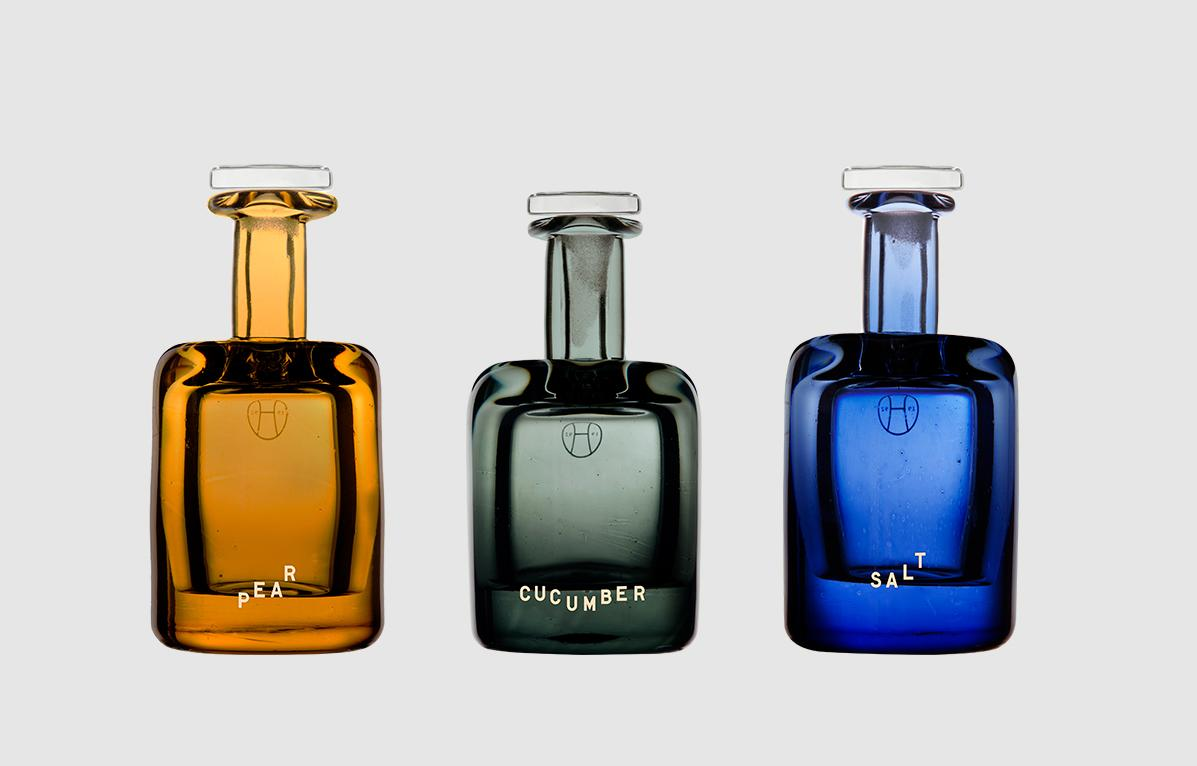 pear perfume in orange glass bottle, cucumber perfume in green bottle, and salt perfume in blue glass bottle