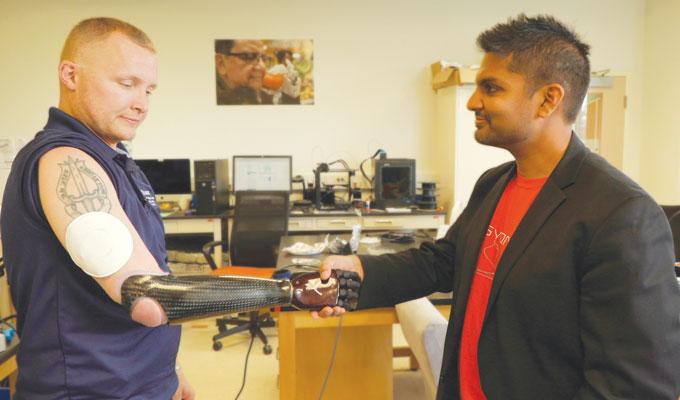 Garrett Anderson shakes hands with researcher Aadeel Akhtar
